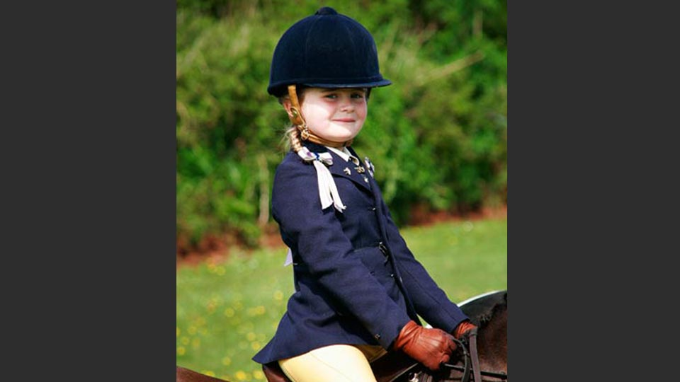 A location portrait of a little girl eventing on her pony.